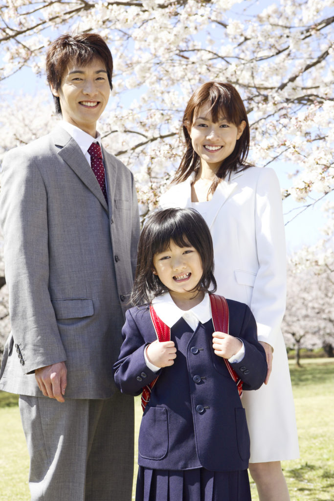 A girl and her parents are in front of Cherry tree