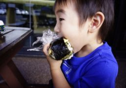 a child eats a big ONIGIRI rice ball