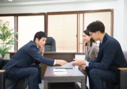 ソファに座って商談するビジネスパーソン3人の写真