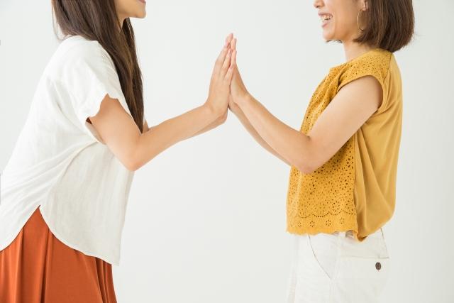 手を合わせて楽し気な女性二人の写真