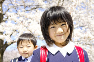 Girl and Boy First Graders are in front of Cherry tree