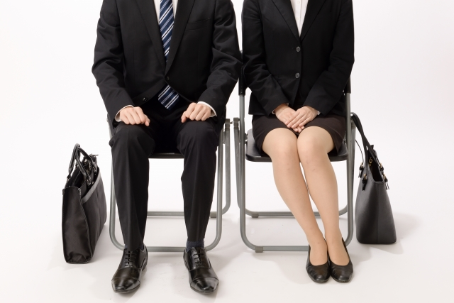 Man and Woman are sitting on the chair with suits