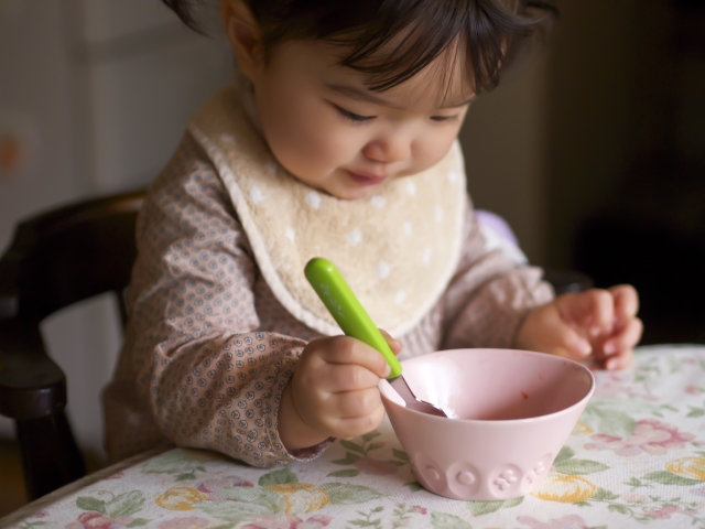 a baby is eating by herself