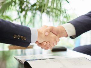 固い握手を交わすビジネスパーソンの手元の写真