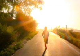 太陽に向かって走る人後ろ姿の写真