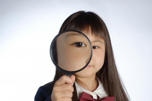 女の子が虫眼鏡で目を拡大させている写真