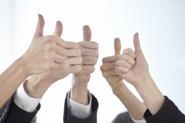 親指を立てた右手を高く掲げあっている写真