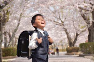 桜を見上げる小学1年生の写真