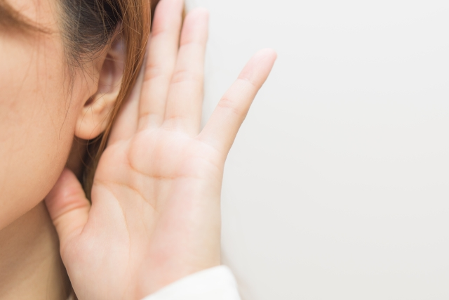 耳を澄ましている女性の耳と手元の写真