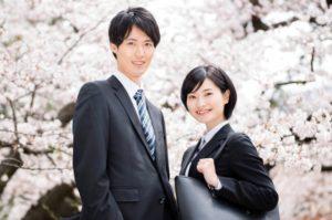 桜の前に佇む新入社員男女の写真