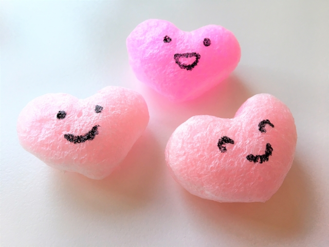 笑顔で場を盛り上げる。イメージ写真ピンクのコットンの笑顔のハートたちの写真