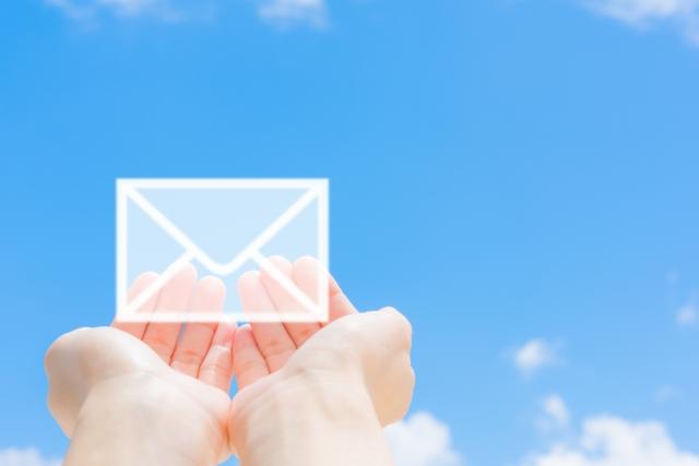 青空を背景にメールをもつ両手の写真