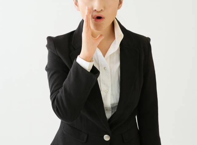 口元に手を当てて話しかけようとするスーツ姿の女性