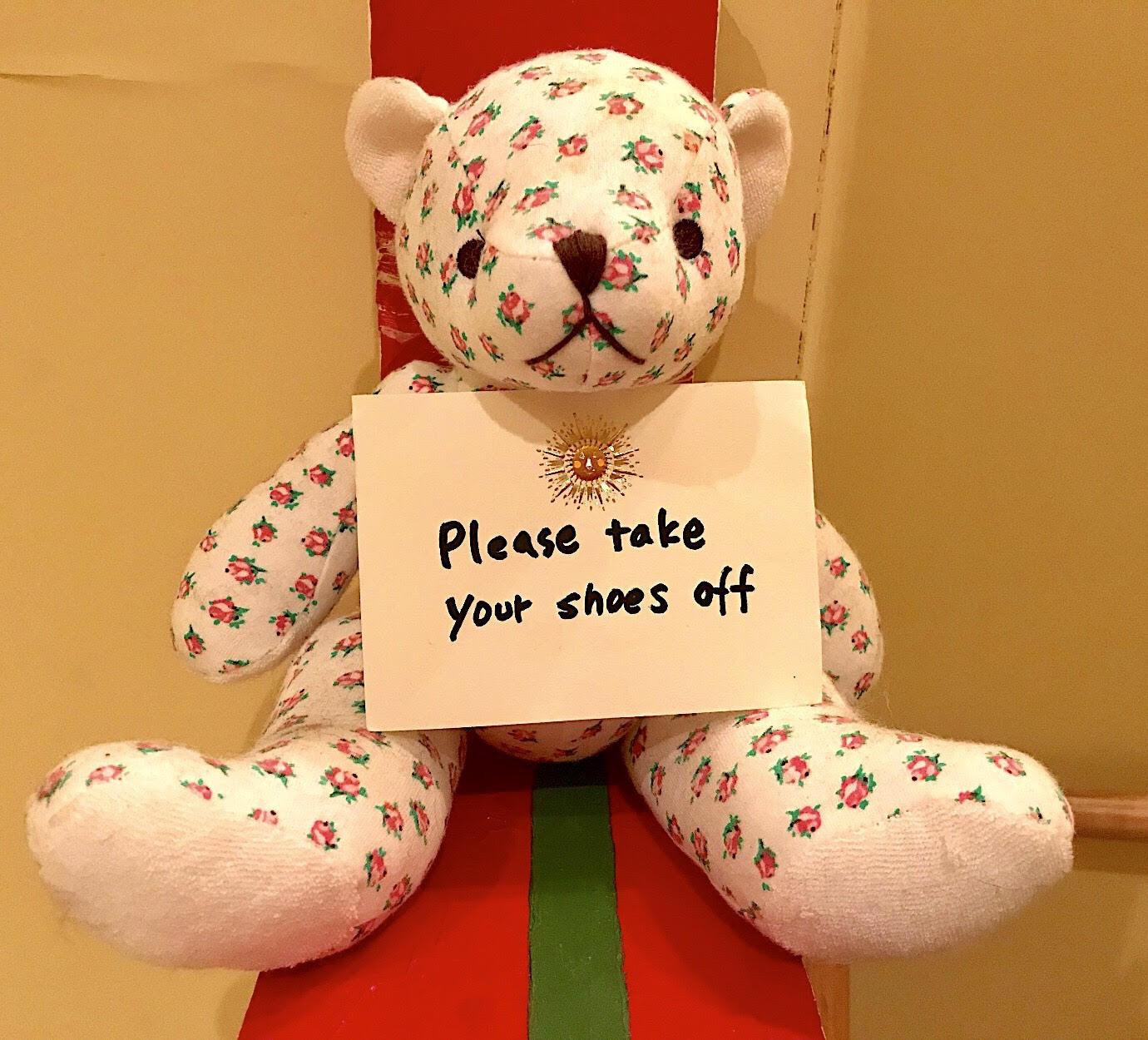靴を脱いでくださいとの英語の看板を掲げる熊のぬいぐるみ