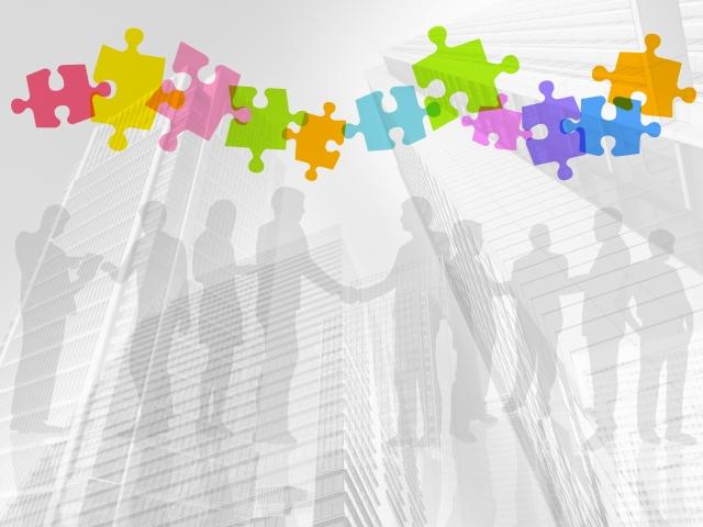 大勢の人のシルエットとパズルのピースで伝わるコミュニケーションをイメージした写真
