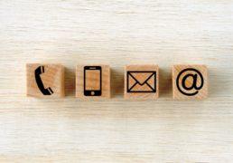電話・スマホ・メール・アットマークのアイコンがプリントされた木のキューブ