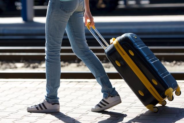 スーツケースを引っ張って歩く足元の写真