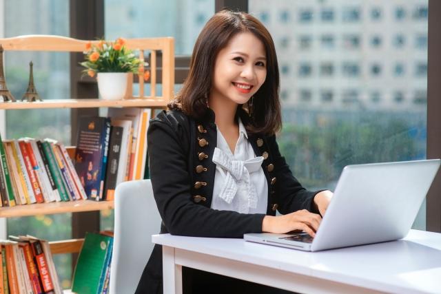 笑顔でパソコンを操作する女性の写真