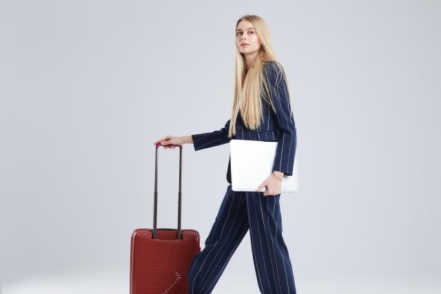 スーツケースとかっこよく立つ女性の写真