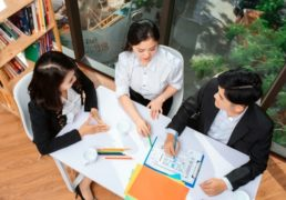 テーブルを囲んで仕事するビジネスパーソン