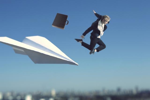 紙飛行機と空飛ぶビジネスマンの画像