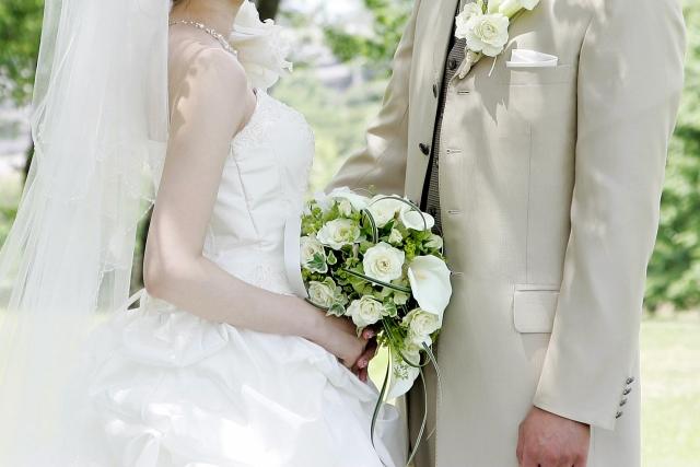 ウェディングドレスとタキシード姿で向き合う男女のイメージ画像
