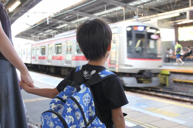 お母さんの手を握り電車を見つめる男の子の後ろ姿
