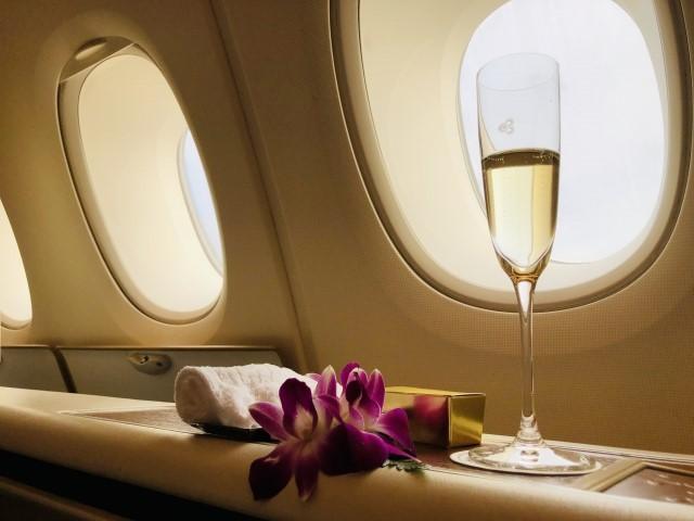 飛行機の窓辺にあるシャンパングラスの写真
