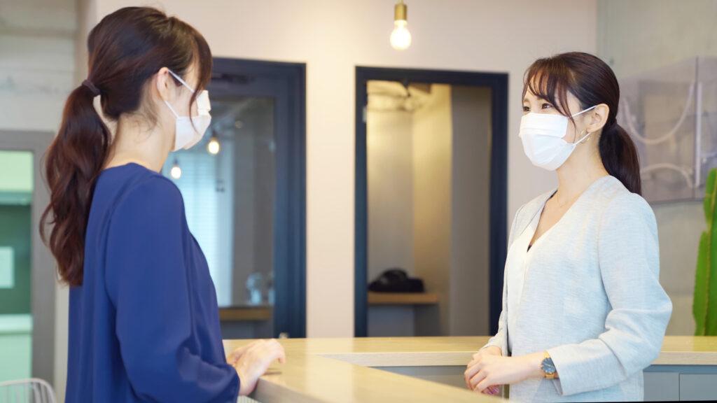 マスクをつけた受付・フロントだけど笑顔の女性たち