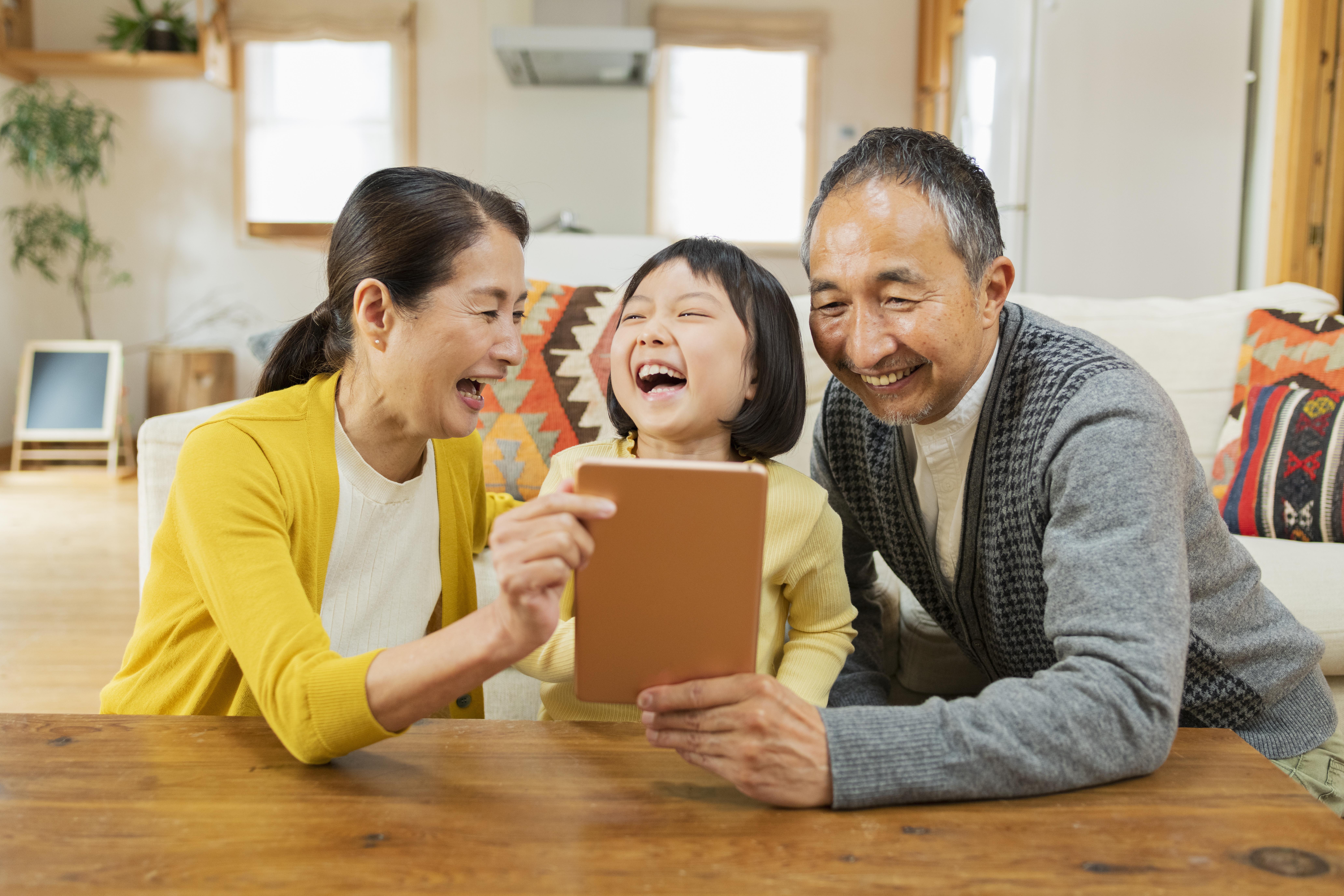 タブレットを楽しそうに触る祖父母と孫