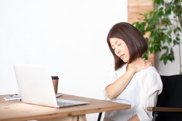 パソコンの前で辛そうに肩揉む女性