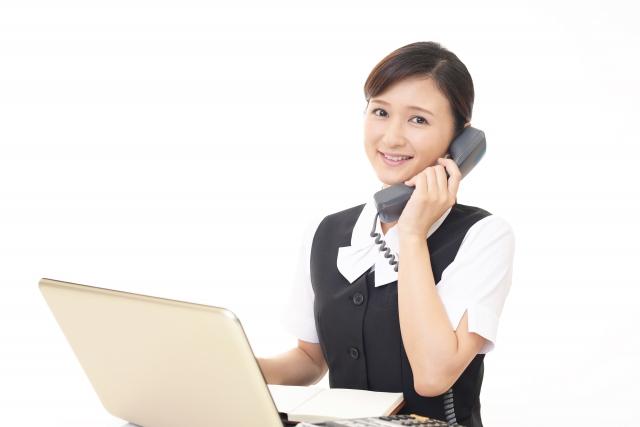 パソコンの前で電話予約するイメージ写真