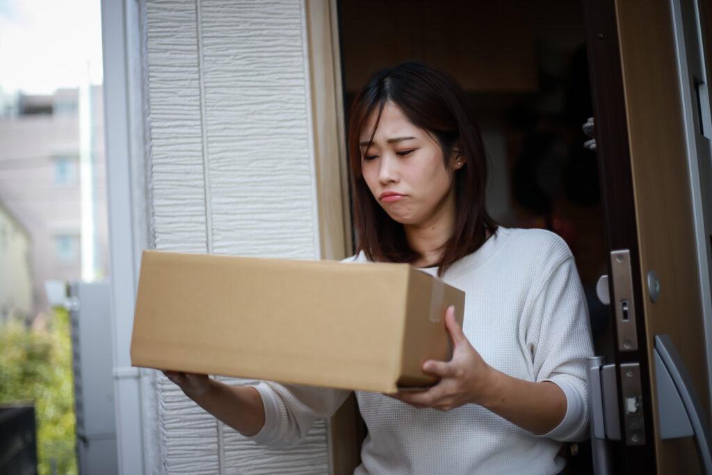 不信な荷物を訝しむ女性
