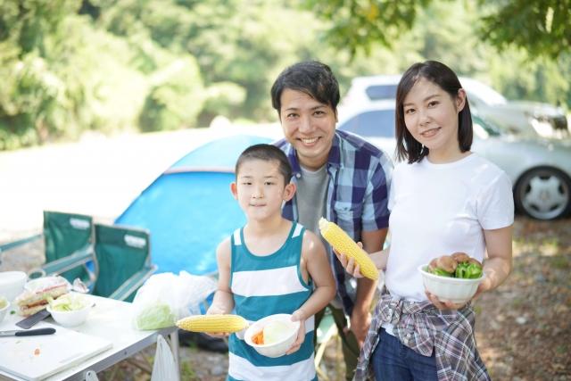 キャンプ場で微笑む家族の写真