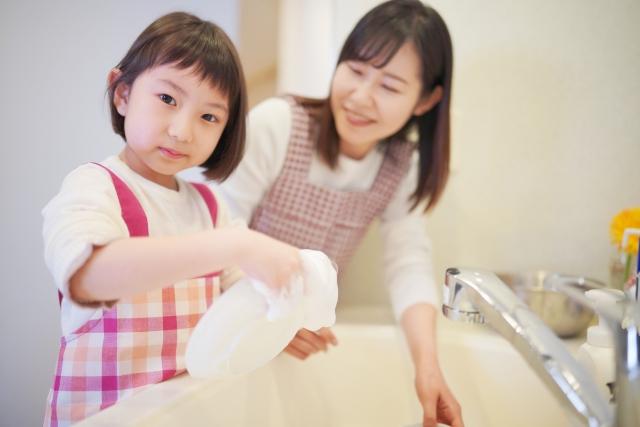 食器洗いお手伝いする女の子と見守る保護者