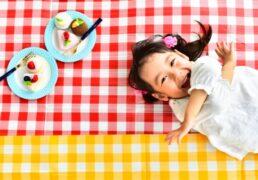 ギンガムチェックの敷物の上で寝ころびピクニックを楽しむ女の子の写真