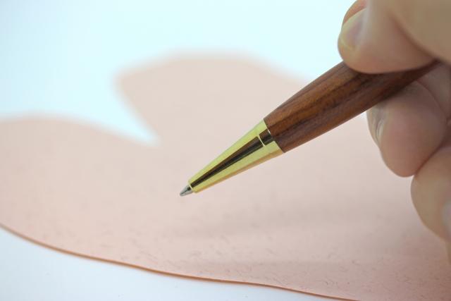 文字を書くためにペンを握った手元