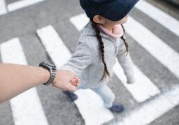 手をつないで横断歩道を歩く女の子